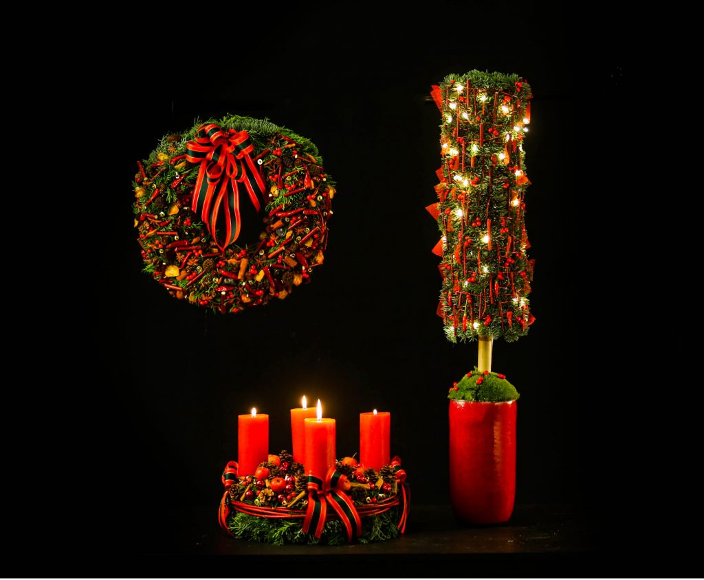 Typical Christmas decorations. A hanging wreath an alternative Christmas tree and a classic wreath with 4 candles on top. All created in a classic red-green setting.