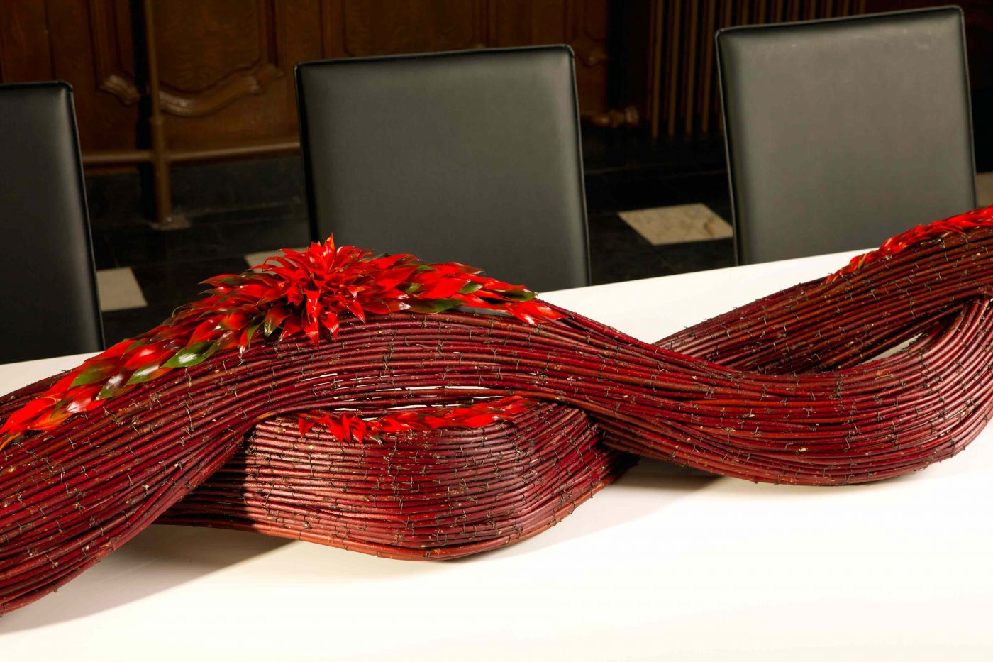 Table decorations are one of the most important subjects in floristry education of the EFDE. Here we see a decoration made of red cornus curling over the table with in the center part red Bromelia flowers used for making a contrast of texture.