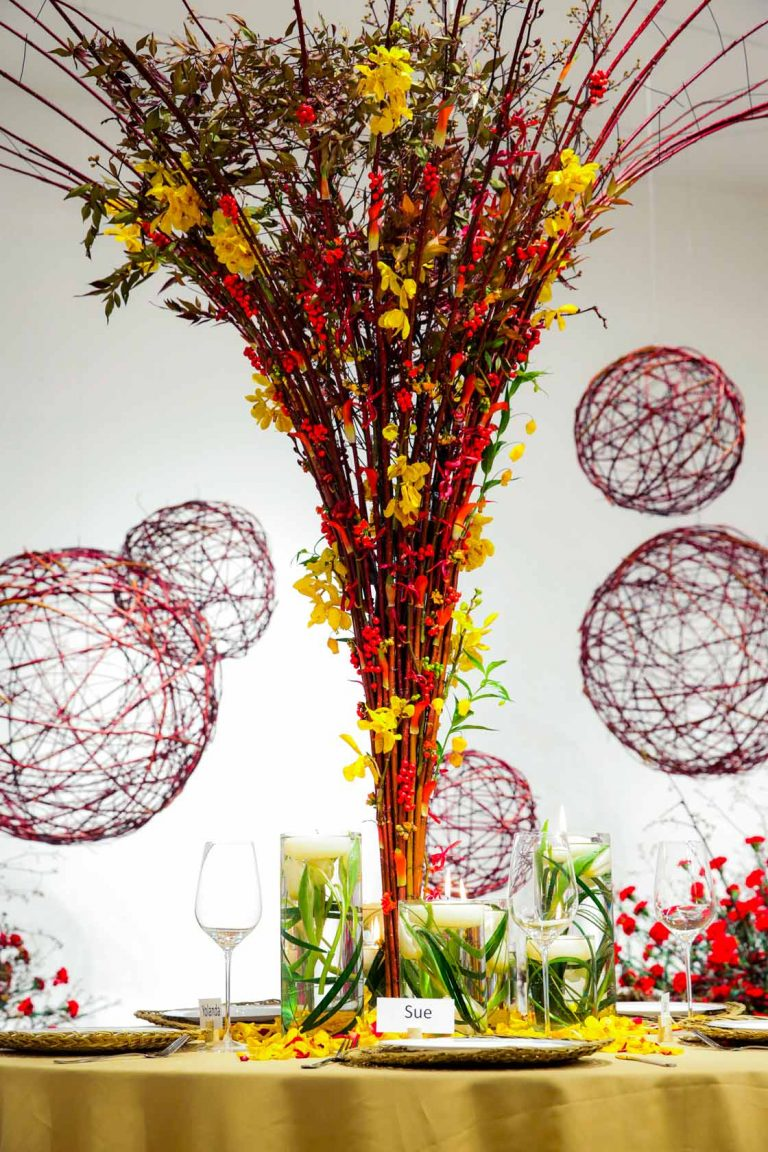 Conical table decoration created in Module 2 of the EFDE build from cornus branches, yellow and red orchids. In the background big red cornus balls.